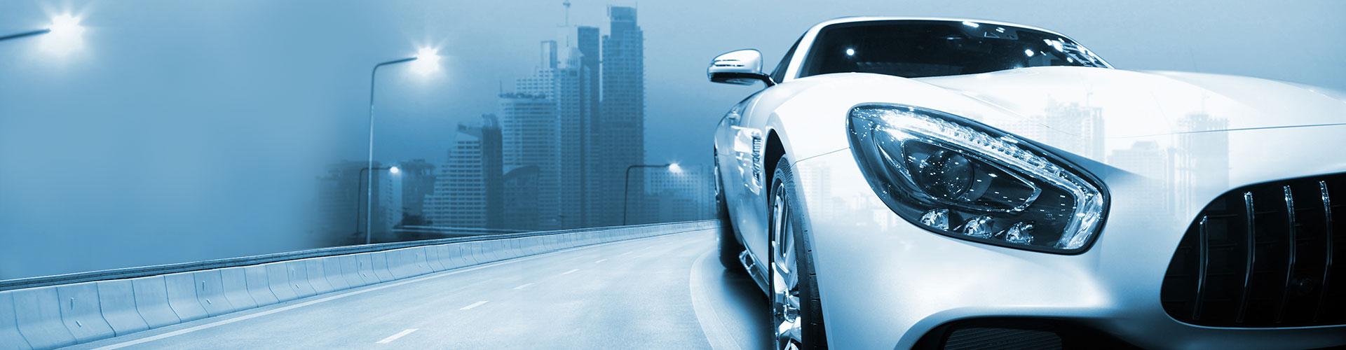 automotive weißes auto auf straße mit skyline im hintergrund